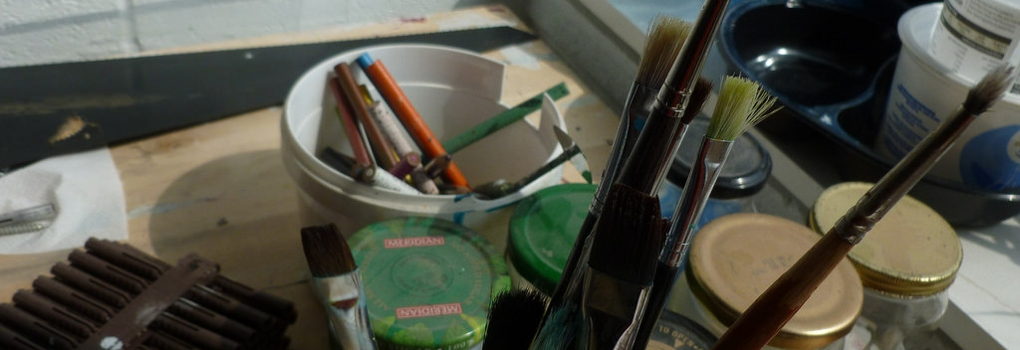 Assorted art supplies and tools on a tabletop
