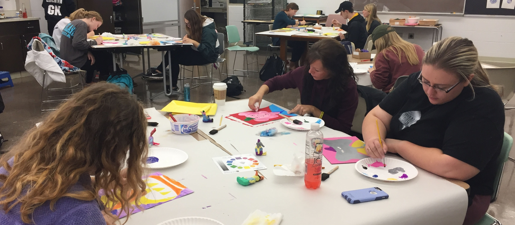 Student teachers and children work on art projects at tables