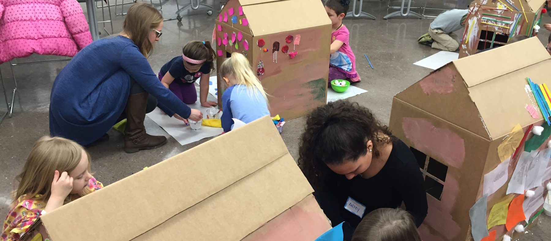 Student teachers and children paint cardboard box houses on the floor