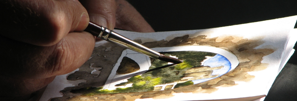 A person holds a paintbrush as a watercolor painting is created
