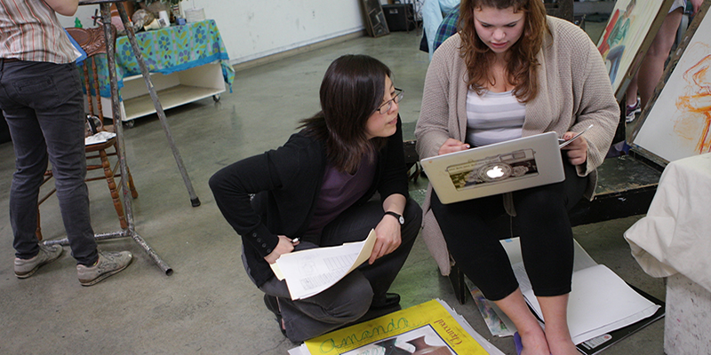 Joomi Chung consults with a student using a laptop as others paint at easels in the studio