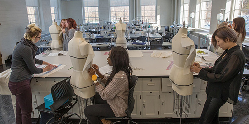 Students pin patterns to dressmakers mannequins in a workroom