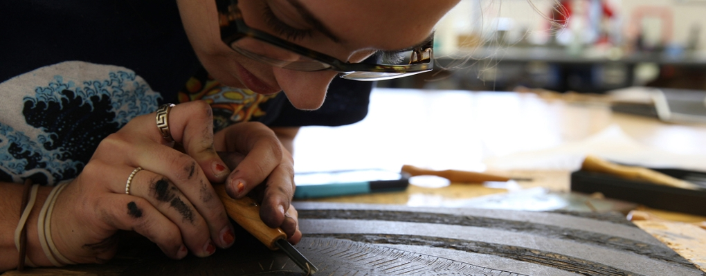 A printmaking student leans close to work on a piece