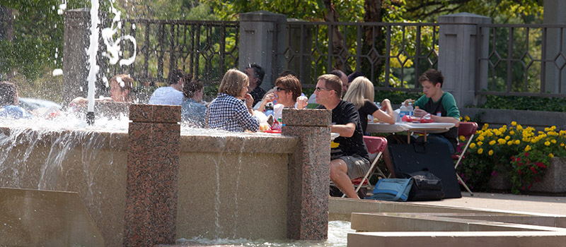 Families eat lunch by the Arts Quad fountain