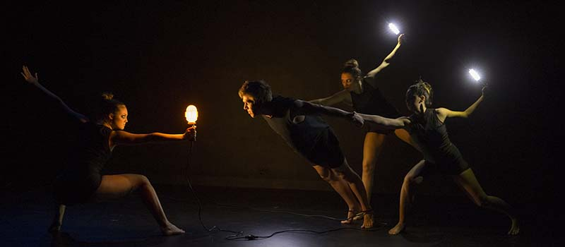 On a darkened stage, dancers pose with lights in their hands