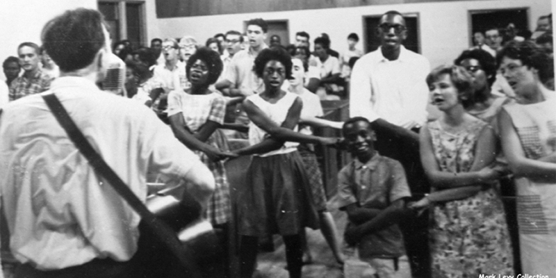 Black and white photo of Freedom Summer participants of all ages clasping hands and singing as a guitarist plays
