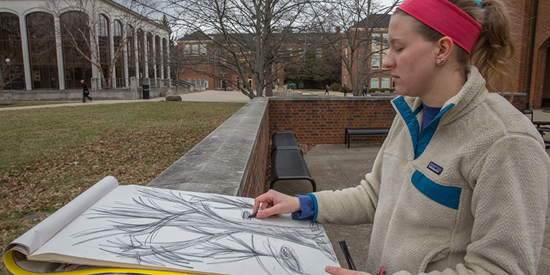 A student works on a sketch near the CPA