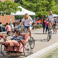 An Arts Day visitor enjoys a ride in an armchair-cycle pedaled by a Miami student