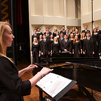 A student conducts a mixed vocal ensemble onstage