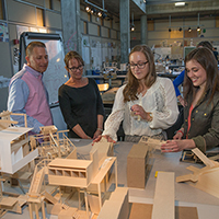 People examine building models in an architecture workshop