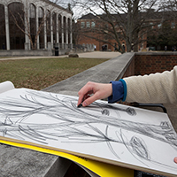 An artist sketches with charcoal near the CPA