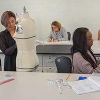 Fashion design students work with dressmakers' dummies and pattern pieces