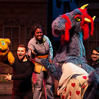 Theatre students manipulate colorful puppets