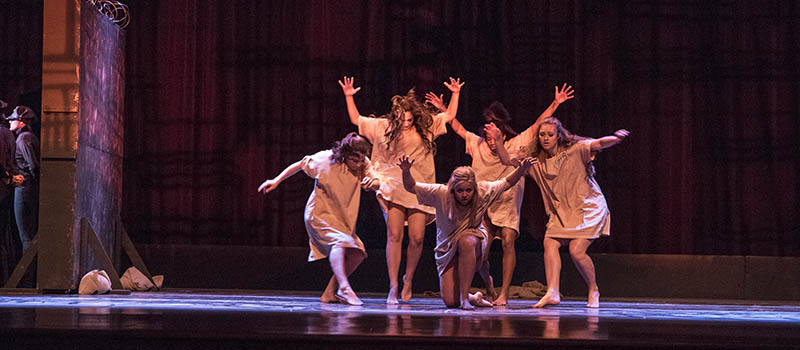 Five dancers with arms outstretched strike a pose onstage