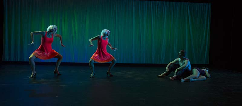 Two dancers in red dresses and blonde wigs move toward figures on the floor of the stage