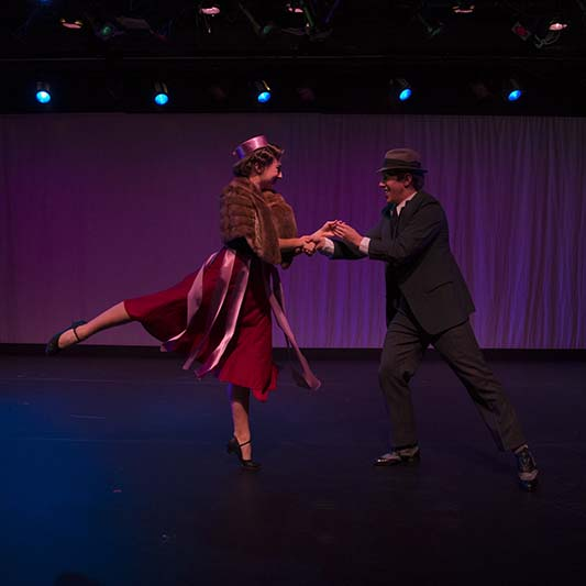 A dancing couple dressed in 40s fashion face each other, holding hands