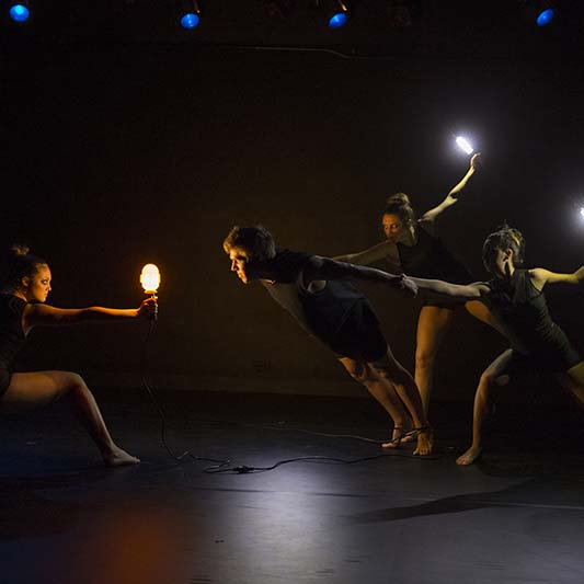 On a darkened stage, dancers perform while holding illuminated devices