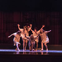 Four dancers pose with outstretched arms onstage, as another crouches in the center