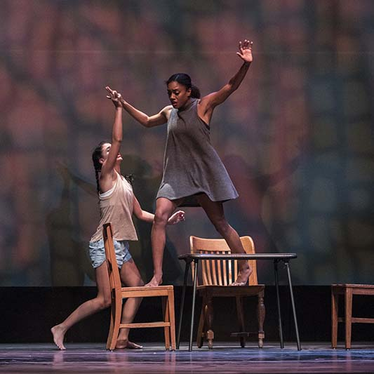 Two dancers perform with a grouping of chairs