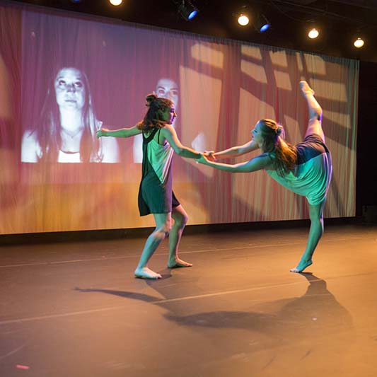 Two women dance as a woman's face is projected on a screen behind them