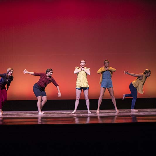 Six dancers perform. Some lean forward and others cross arms across their chests.