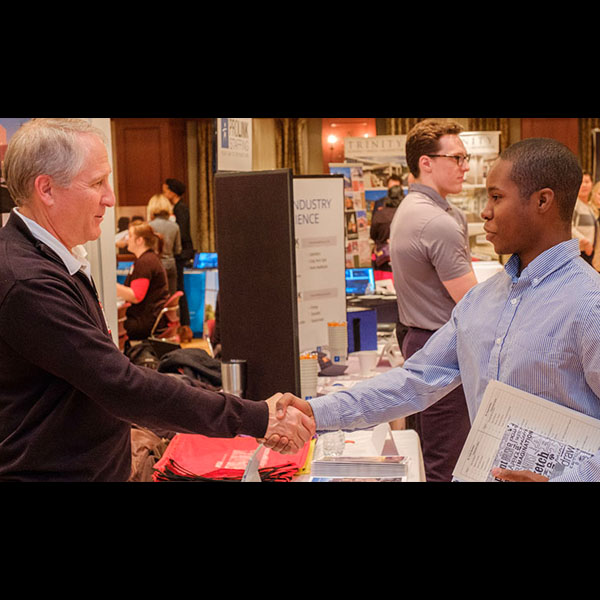An employer and architecture student shake hands at a Miami job fair