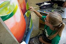 A woman paints a canvas