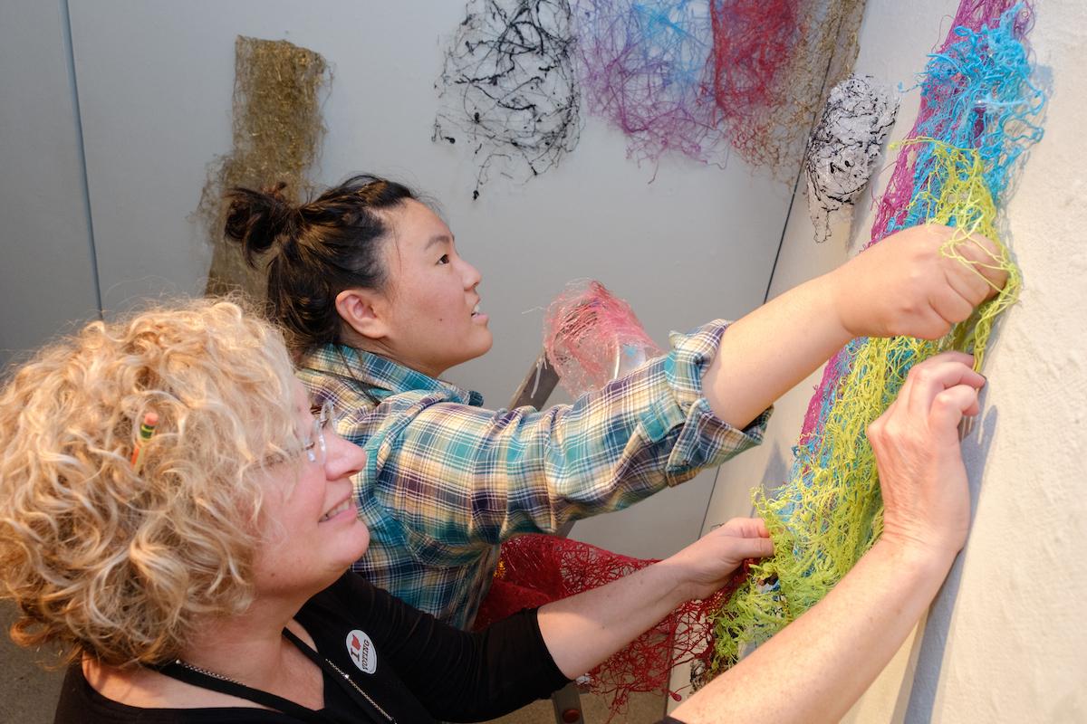 Professor and student install an art capstone exhibit
