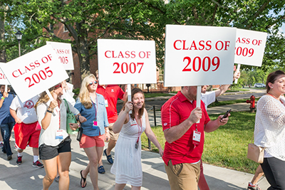 Alumni parade showing individuals carrying class year signs