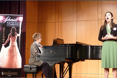 A young woman sings onstage, accompanied by a pianist. Banner at left 'Schmidt Youth Vocal Competition'