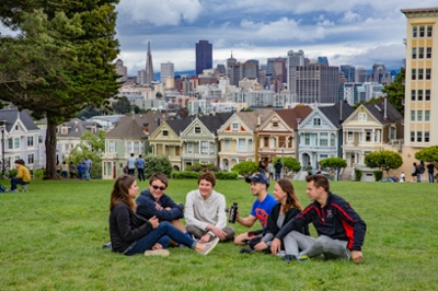 Students sit on a lawn with San Francisco rowhouses and skyline in background