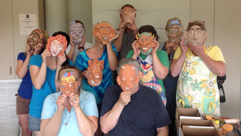 A group of students hold clay masks over their faces as they pose