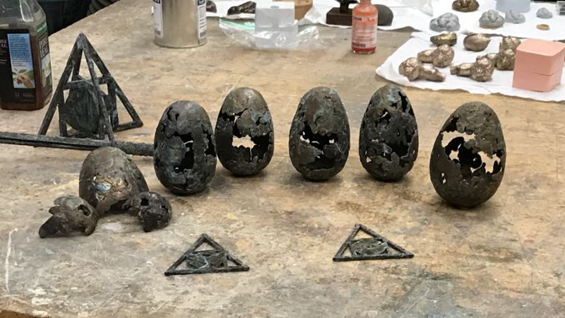 Egg-shaped bronze sculptures on a worktable