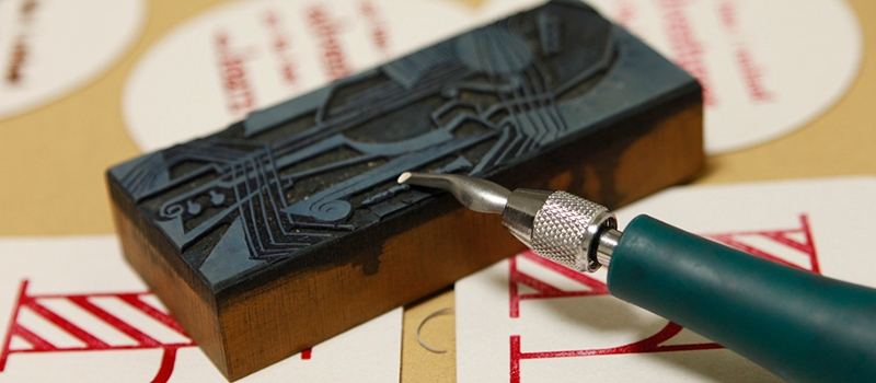 A tool carves an image for printmaking. Assorted letters and prints lie beneath it.