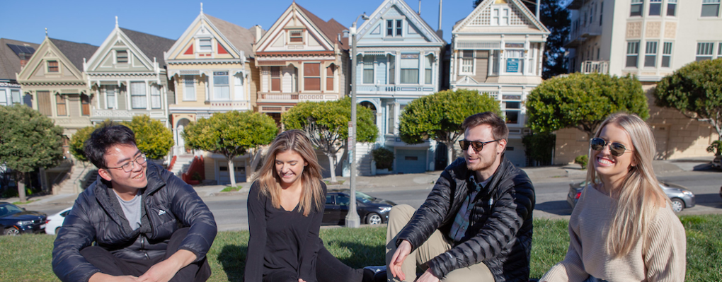 Students relax on the grass near the Painted Ladies rowhouses in San Francisco