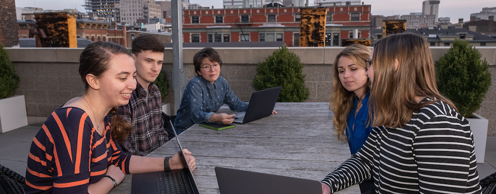 Students collaborate at an oblong table on a balcony in downtown Cincinnati
