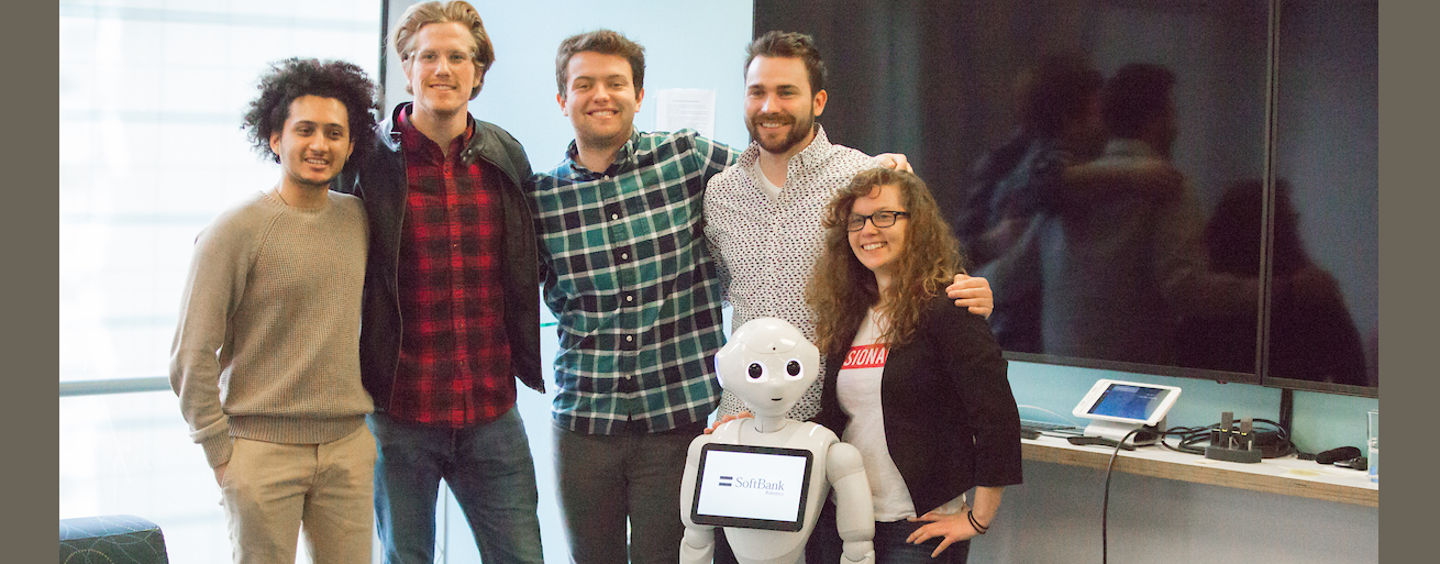 San Francisco students and alumni pose with a humanoid robot
