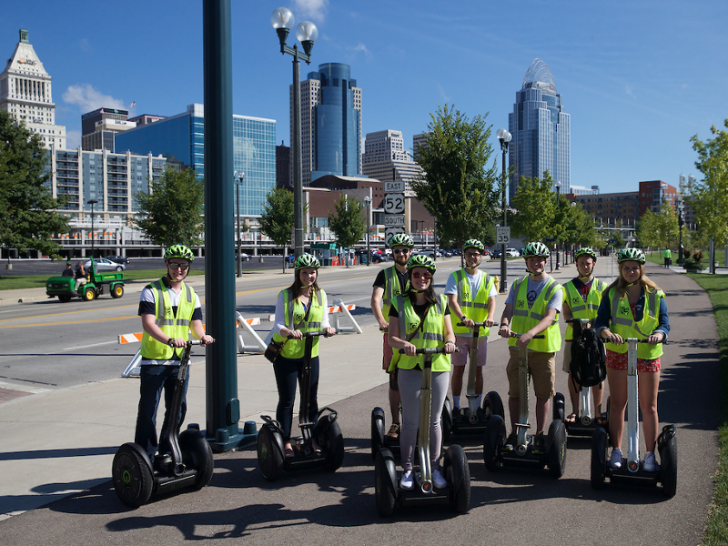 Students on Segways stand in front of the Cincinnati skyline