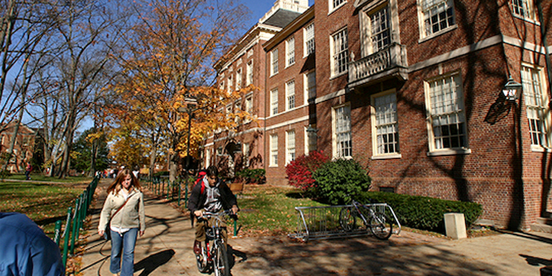 Students walk and bike along a sidewalk near an academic building on Oxford campus