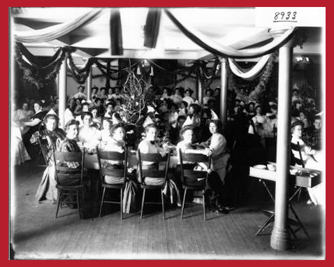Women in Hepburn Hall dining room are seated at rectangular tables. The room is decorated for the holidays. Year 1909.