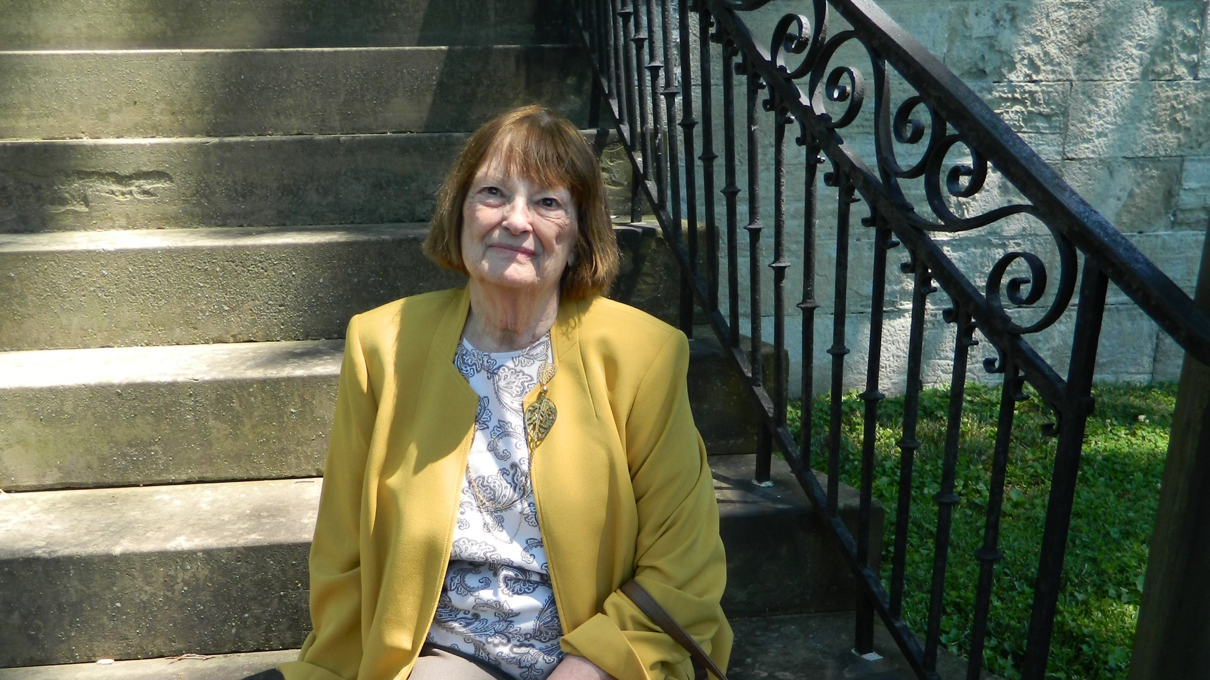 Carol Hennessy takes a break on the steps of Lanier Mansion