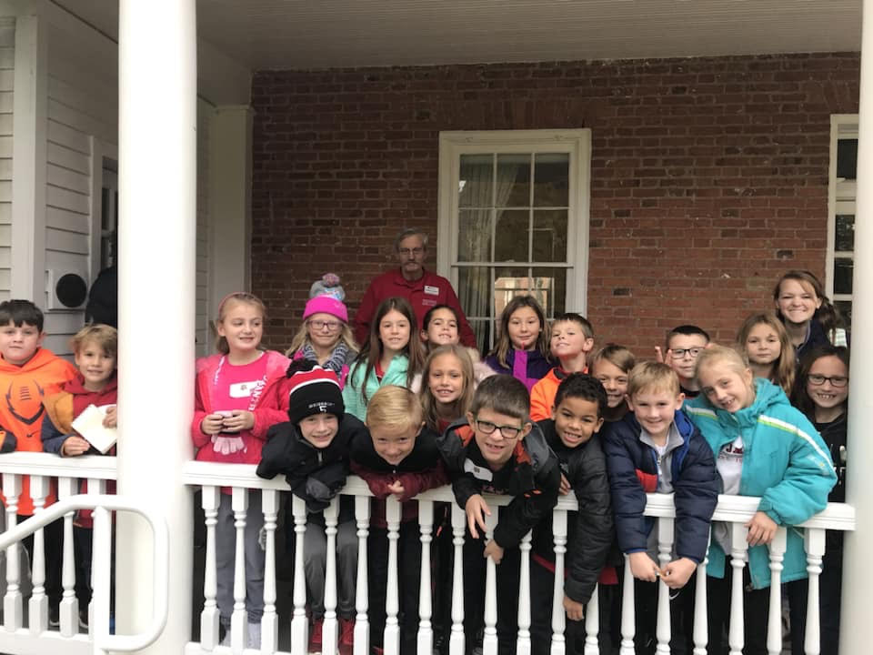 Students, parents, and teachers from St. James School, Cincinnati, pose on the side porch of McGuffey House