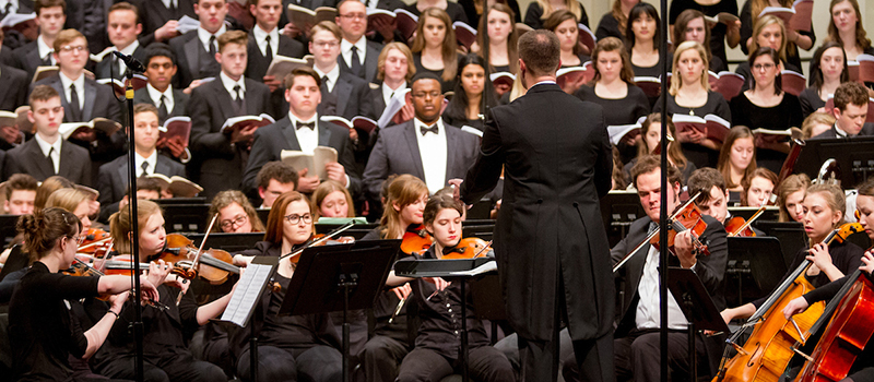 A mixed chorus sings, accompanied by the Miami symphony orchestra onstage at Hall Auditorium