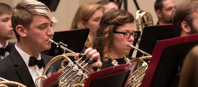 A row of French horn players perform at Wind Ensemble concert