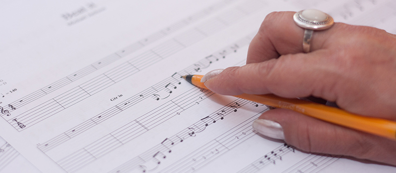 A hand holding a pen pauses over a musical composition
