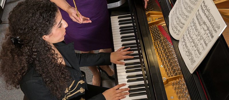 A student plays piano during a lesson