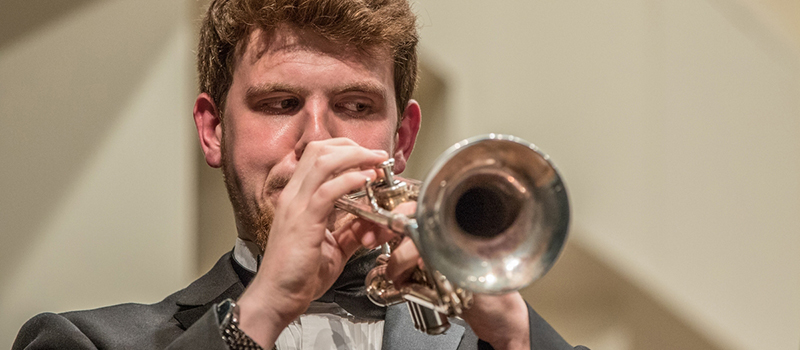 A student plays trumpet during a concert band performance