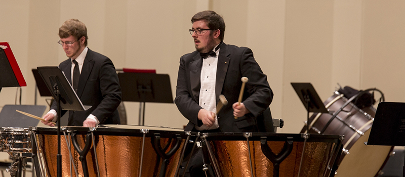 Percussionists perform on snare and tympani during an orchestra concert