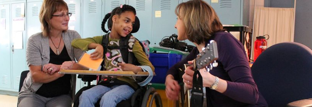 A music therapist plays guitar for a child with a disability as a woman looks on