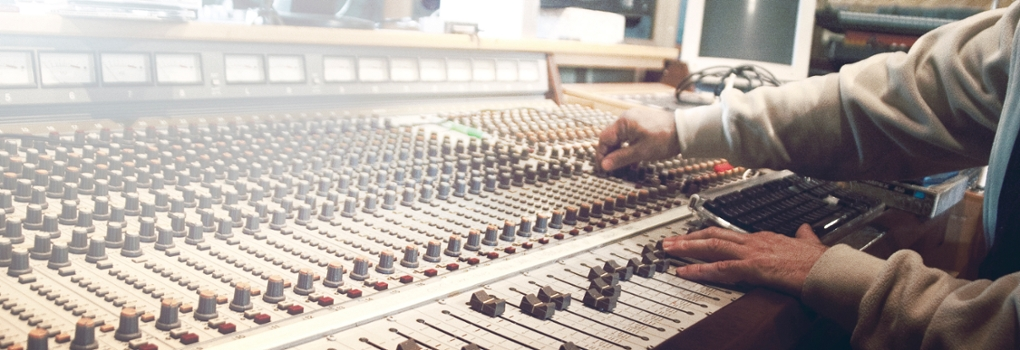 A man operates a soundboard